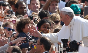 Pope blesses child as he arrives to lead general audience at Vatican